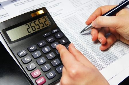 cuadro sinoptico: Calculadora, pluma y documento contable con una gran cantidad de n�meros y manos de mujer Foto de archivo
