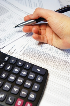 Calculator, pen and accounting document with a lot of numbers and woman hands Stock Photo