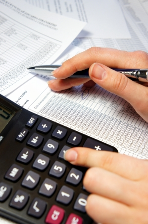 Calculator, pen and accounting document with a lot of numbers and woman hands Standard-Bild