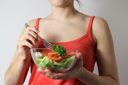 Young woman with vegetable salad in her hands photo