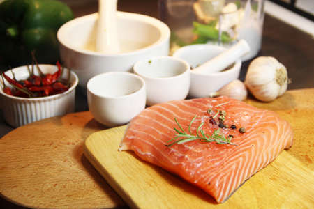 Beautiful filet of salmon and herbs on the wooden background photo