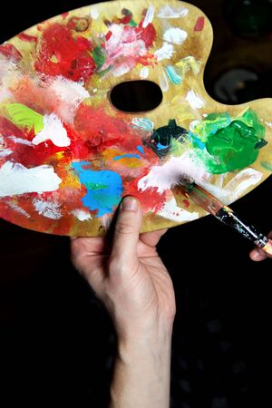 Artist's hand holding a paintbrush and art palette photo