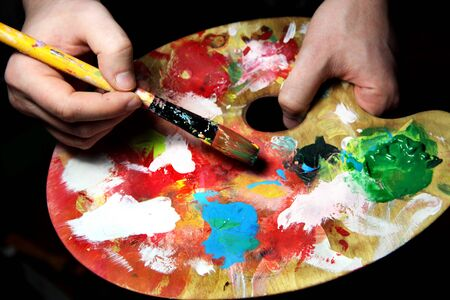 Artist�s hand holding a paintbrush and art palette photo