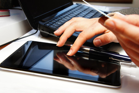 Office table with laptop and notebook with typing female hands