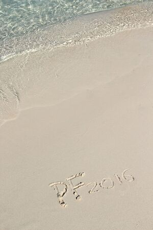 pf: Handwriting inscription PF 2016 on the beach with clean blue water