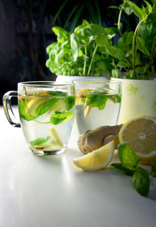 teacups: Two teacups with fresh peppermint, ginger and lemon on the table