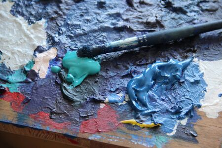 Art palette and paintbrushes in painter studio