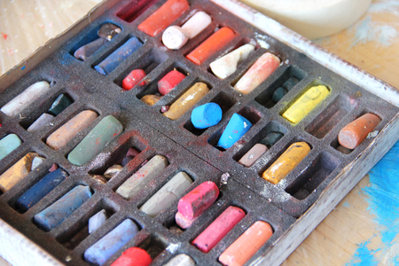 Art palette and pastels in painter studio