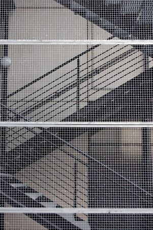 metallic stairs: Metallic stairs of the office building behind net Stock Photo