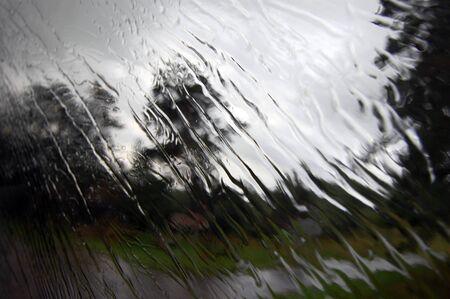 kropla deszczu: Heavy rain is falling under the window glass Zdjęcie Seryjne