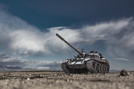 Military or army tank ready to attack moving over a deserted battle field terrain