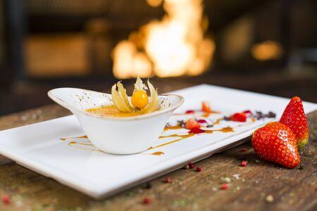 Creme brulee (cream brulee, burnt cream) served on wooden table.