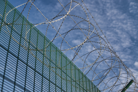 Top security spiral barbed wire border fence Stock Photo
