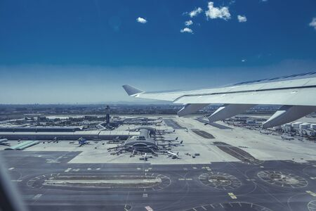 An aerial picture of the airport territory, buildings and runway taken from the airplane window during take-off with the wing visible. Editorial