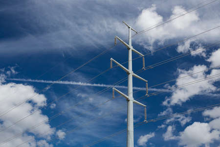 A photo of high voltage power lines with clouds and blue sky as a background