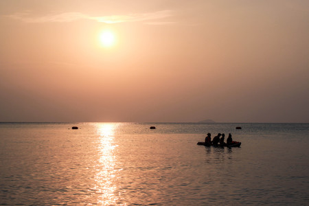 cayak: Four people on cayak in the sea with sunset. Stock Photo