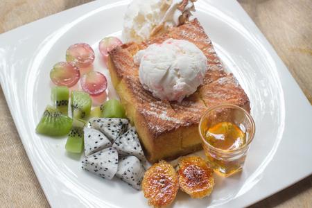 Honey toast on white dish with  banana, kivi, grape and icecream.