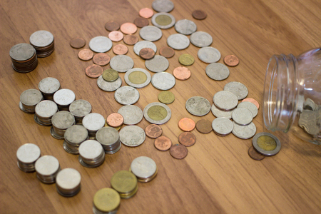 Thai baht coin out of the glass jar on wooden floor. Stock Photo