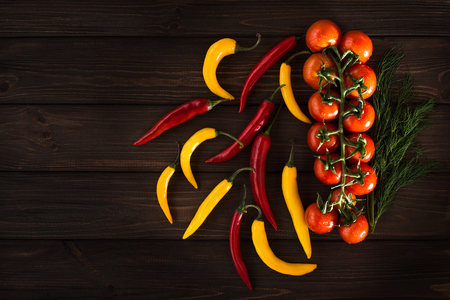 poignant: Yellow and red chili peppers on a wooden dark background. Free inscription