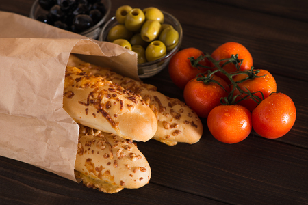 A fragrant Italian bread with baked cheese, a branch of tomatoes and olives on a wooden dark background. The Italian menu. Ingredients