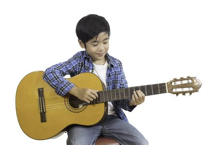 A portrait of a cute Asian elementary school boy wearing a jeans and a plaid shirt with his guitar. An isolated image with white background