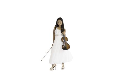 A portrait of a cute, elementary school Asian girl with long hair and wearing a white evening dress holding her violin. An isolated image with white background