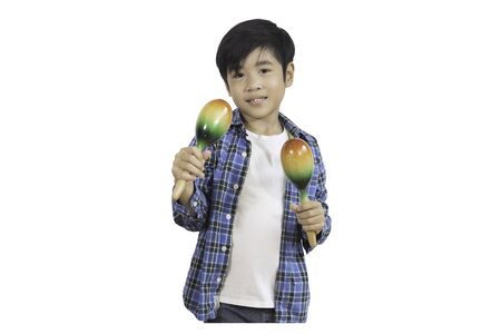 Portrait of a cute Asian elementary school boy wearing a jeans and a plaid shirt with maracus, a musical instrument that shakes to make sounds. An isolated image with white background