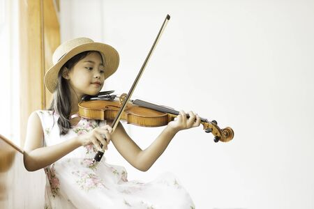 A cute Asian elementary school girl is playing a violin happily in her home.