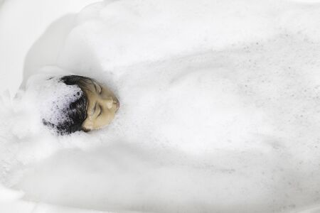 An Asian girl is happily soaking in a bubble bath.