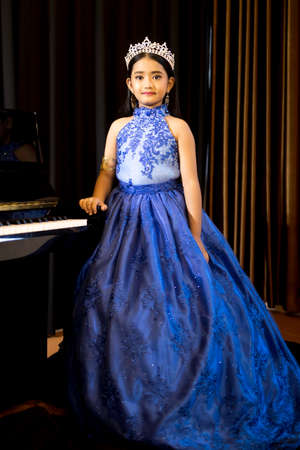 A portrait of a cute Asian girl, makeup, wearing a blue evening dress and a crown standing beside the piano in the room.