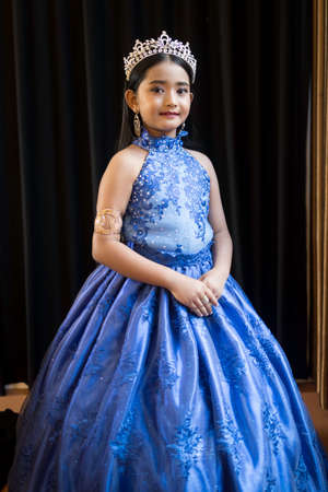 Portrait of a cute Asian girl, makeup, wearing a blue evening dress and a crown.