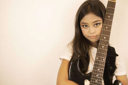 A portrait of a cute Asian girl in a make-up standing to hug her electric guitar.