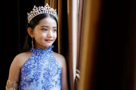 A portrait of a cute Asian girl, makeup, wearing a blue evening dress and a crown standing by the window.