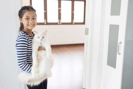 A cute Asian girl is holding her white cat inside a white painted wall house.