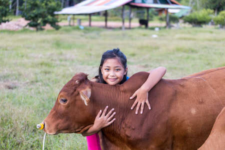 An Asian girl lovingly hugs her cow in a ranch. The concept of animal love. Stockfoto