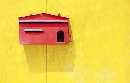 Red mail box on old yellow wooden door photo