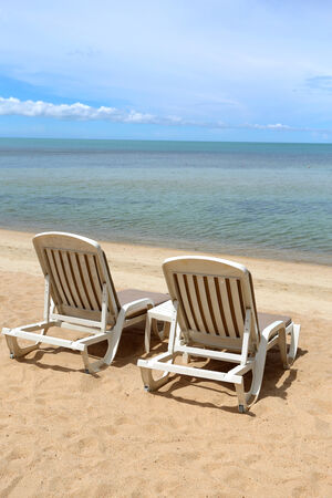 lovely white lounge chairs on the sea beach