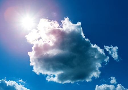 Beautiful summer photo of sun and clouds on a blue background