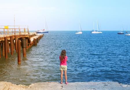 Photo of a standing girl on a dock near the blue sea
