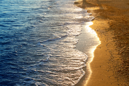 Photo of a background of a bright sunlit wave on the seashore