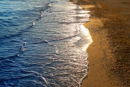 海岸の明るい太陽に照らされた波の背景の写真