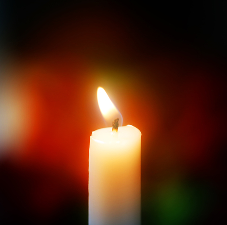 Photo background with a burning white candle on a blurred background