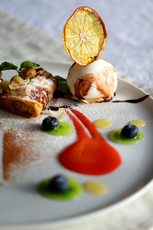 Photo of a bright dessert pie with apples and ice cream on a white plate Stock fotó
