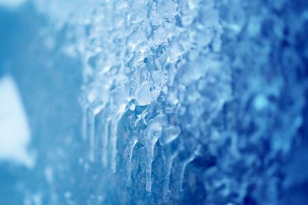 Fotoachtergrond van heldere ijskegels en ijsschotsen op de omheiningen dichtbij de rivier Stockfoto