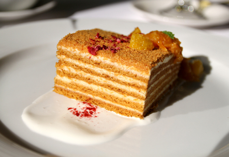 Macro photo of tasty honey cake with orange sunlit at restaurant