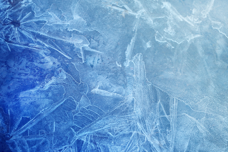 Photo background bright blue frosted thin ice with cracks in the spring