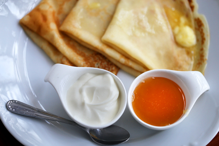 Photo of macro delicious Russian pancakes with honey and sour cream