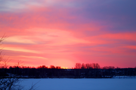 Photo of a bright red dawn over the river in spring