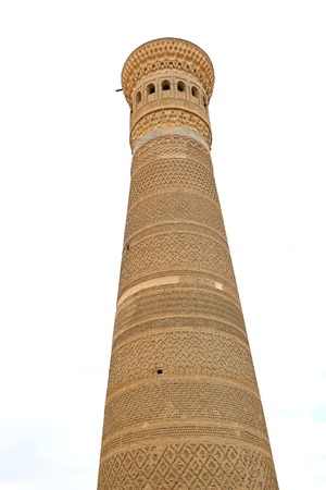 Photo of an ancient beautiful Oriental minaret in Uzbekistan Stock Photo