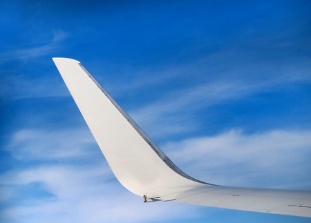 Photo beautiful white fragment of the aircraft wing in the air Stock Photo